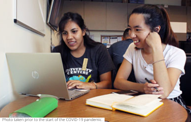 Two UC San Diego students talk, sitting at a desk in front of a laptop